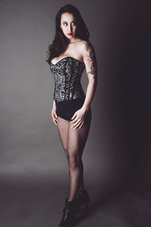 Photo of Woman in Black Floral Corset, Black Panties, and Black Pantyhose Posing In Front of Gray Background