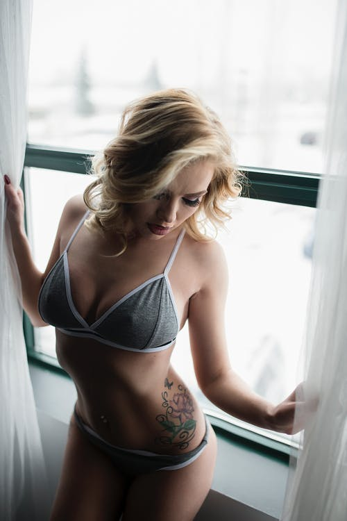 Photo of Woman in Gray Bra and Pantie Holding a Curtain Beside a Window