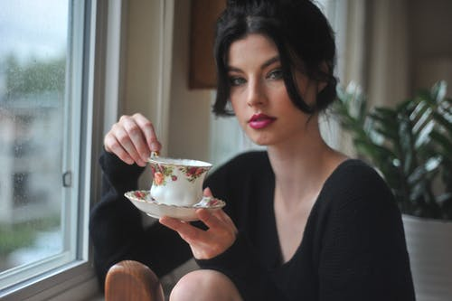 Woman Holding White Saucer And Teacup