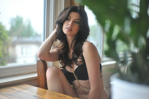 Photo of Woman in Black Bra Sitting on Wooden Chair Next to a Window