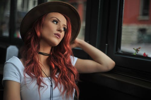 Photo of a red-haired woman looking outside a glass window