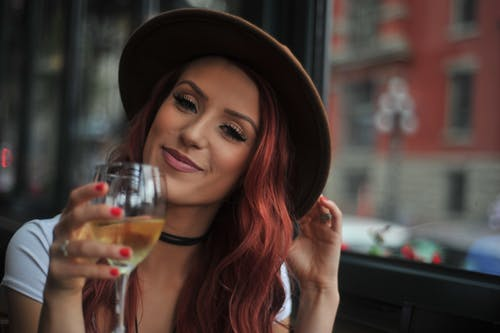 Portrait photo of a woman holding wine glass near a glass window