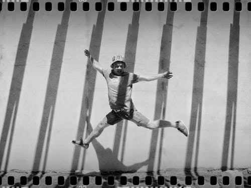 Grayscale Photo of Jumping Man Beside Concrete Wall