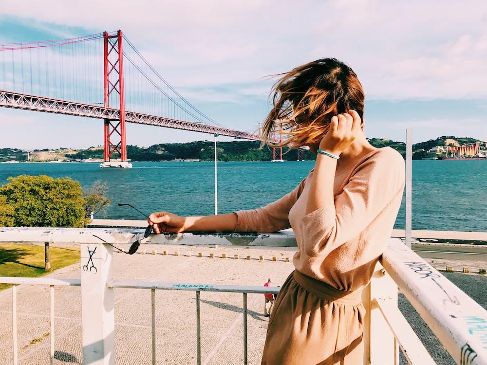 Woman in Beige Shirt and Brown Skirt Standing in Balcony Overlooking Bridge in Bay