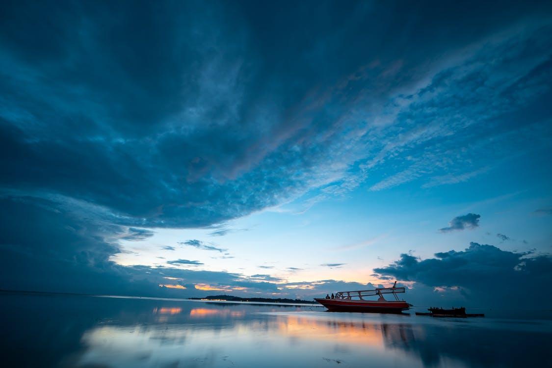 Foto Perahu Di Perairan Tenang Di Bawah Langit Biru