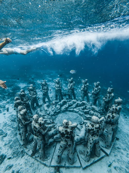 Grey Statues in Middle of Ocean