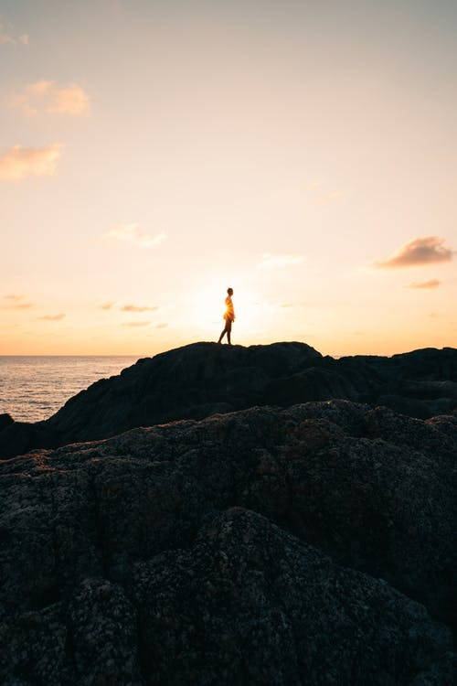 Person Standing on Rock Mountain Fronting the Sea