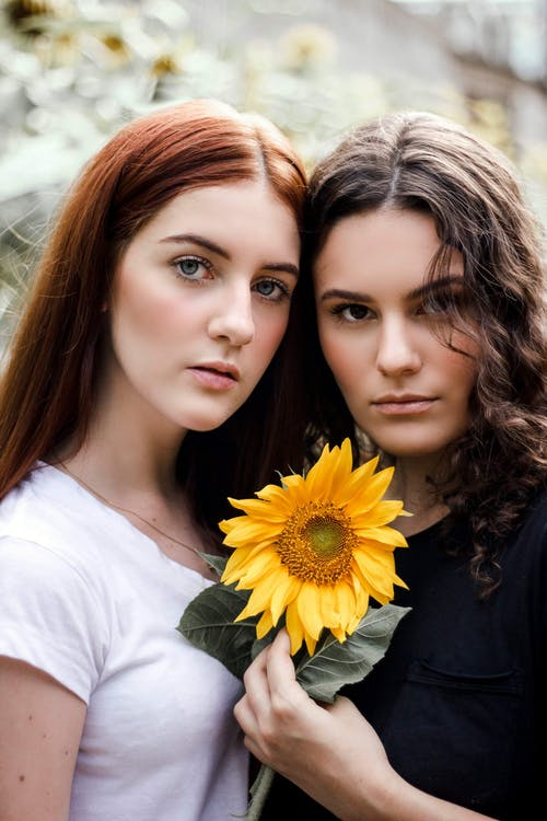 Photo of Two Women Holding Yellow Flower