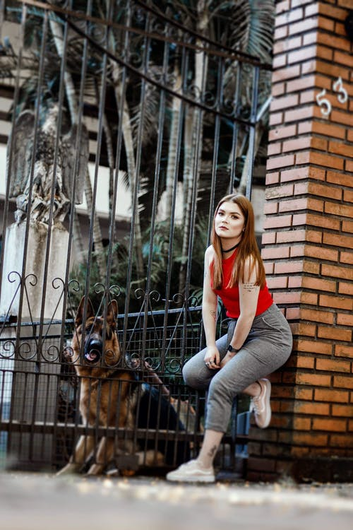 Photo of Woman Leaning Beside Gate With German Shepherd