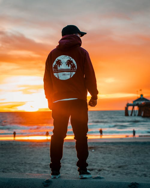 Photo of Man in Hoodie and Cap Standing at the Shore During Golden Hour