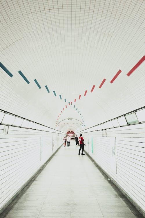 Men Walking Along Tunnel