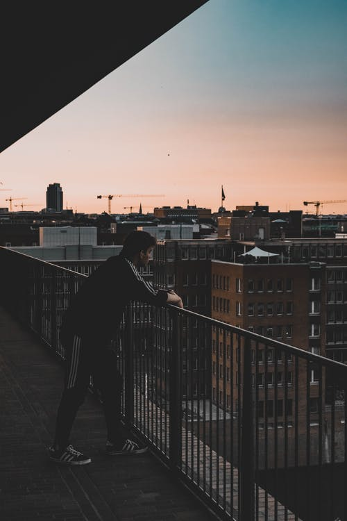 Photo of Man in Black and White Tracksuit Leaning on Balcony Railings