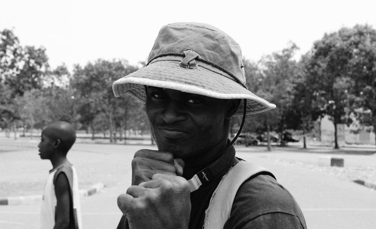 Grayscale Photo Of Man Showing Fist Wearing Hat