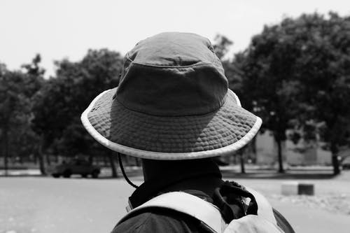 Grayscale Photography  of a Man  Wearing Hat Near Trees