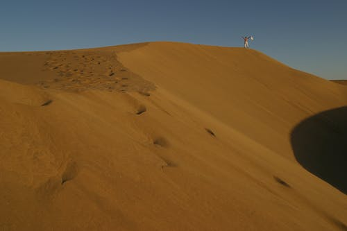 Landscape photo of a man standing on a sand dune on a desert