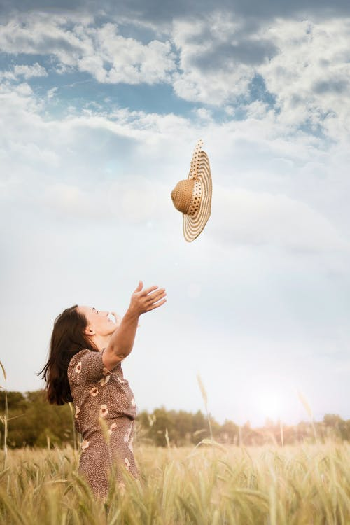Woman Standing on Wheat Field Throwing Brown Sun Hat on the Air Under White and Blue Skies