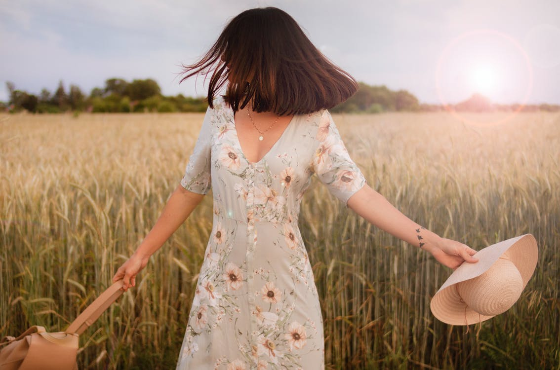 Woman in Multicolored Floral Dress Standing in Middle of Crop Field Holding Straw Hat