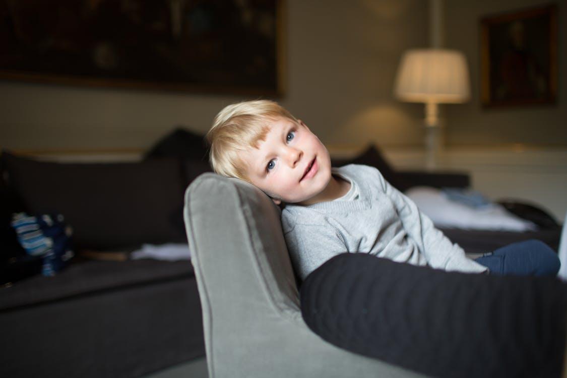 Boy Seated on Sofa