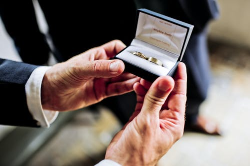 Photo of Person Holding a Black and White Case with Two Gold Rings