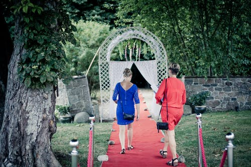 Two Women Walking on Red Carpet Leading Inside White Gate