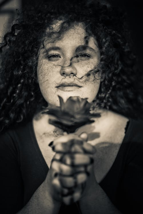 Grayscale Portrait Photo of Woman With Freckles Holding Flower