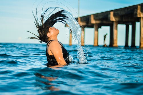 Time Lapse Photography Of Woman Flipping Her Hair While Bathing In The Sea