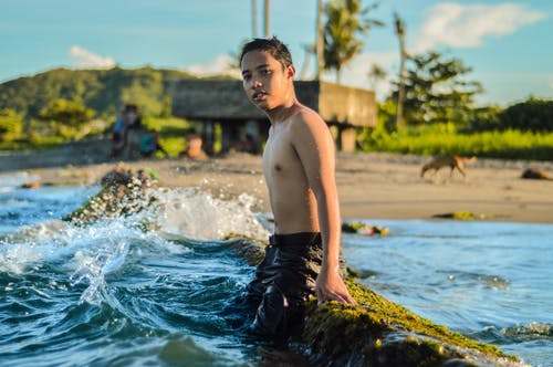 Topless Boy Sitting on Rock Beside Body of Water Viewing Mountain