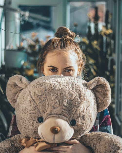 Woman Covering Face With Big Bear Plush Toy
