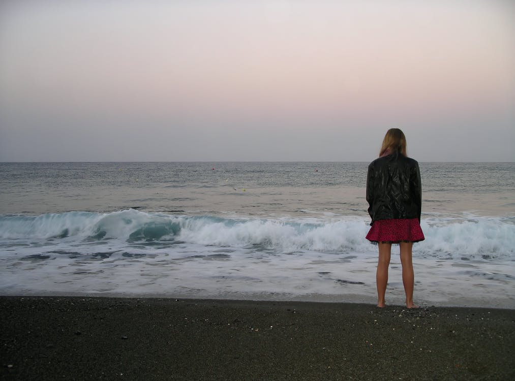 Back View Photo of Barefoot Woman in Black Leather Jacket and Standing by the Beach Looking at the Horizon