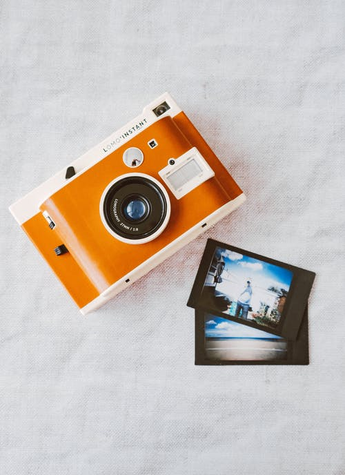 Orange and White Instant Camera on White Cloth