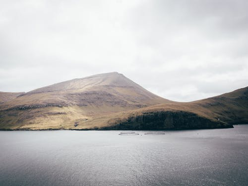 Body of Water and Mountain Under Grey Sky