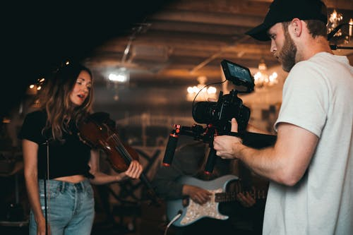 Man Taking a Video of a Woman Carrying a Violin