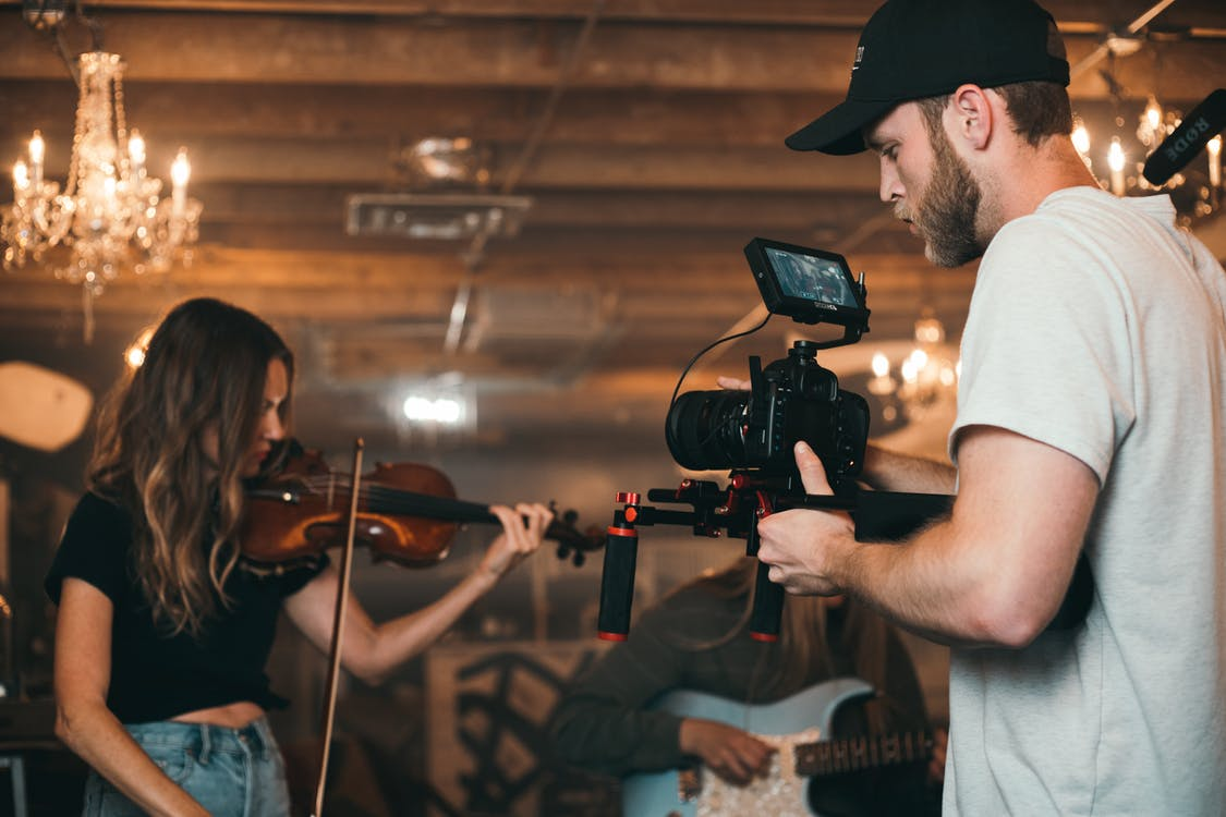 Man Holding Camera and Woman Playing Violin