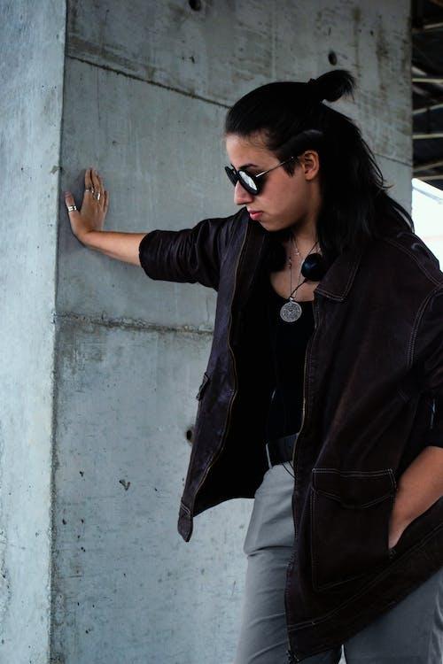 Безкоштовне стокове фото на тему «бетонна стіна, брюнетка, вуличний одяг, дивитися вбік»