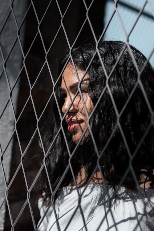 Close-up Portrait Photo of Smiling Woman Standing Behind Chain-link Fence Looking into the Distance