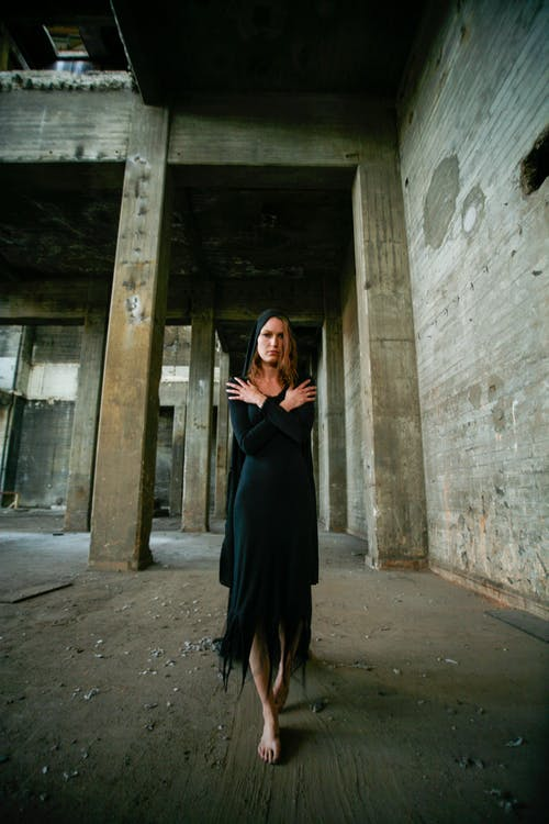 Photo of Standing Woman in Black Dress Walking Barefooted in Abandoned Building