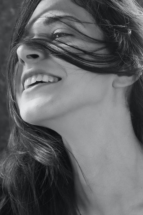 Grayscale Close-up Photo of Smiling Woman's Face