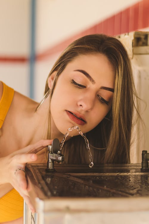 Close-Up Photo of Woman Drinking On Drinking Fountain