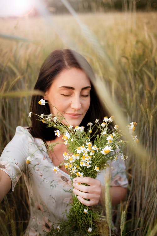 Photo of Woman Holding White Flowers