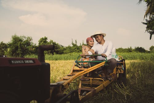Photo of a Couple Riding on Tractor