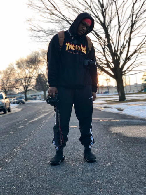 Photo of Man Wearing Hoodie Standing on Road