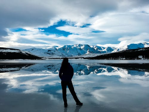 Silhouette Photo of Woman Facing Snow Capped Mountain