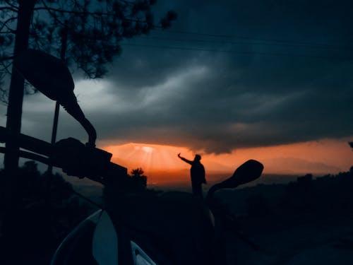 在黑暗陽光明媚的晚上拍照的傢伙 的 免費圖庫相片