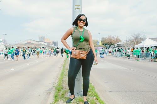 Photo of a Woman in Green Sleeveless Top and Black Leggings Standing by Metal Pole