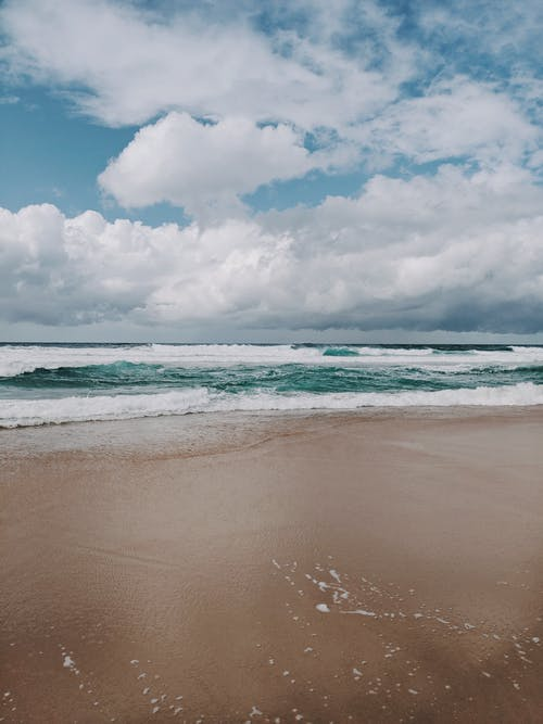 Photo of Seashore Under Cloudy Sky