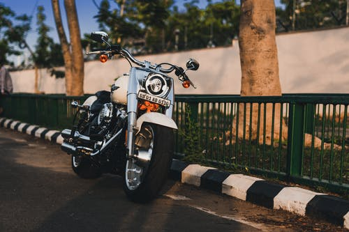 Photo of White Harley Davidson Fatboy Cruiser Motorcycle Parked by Curb