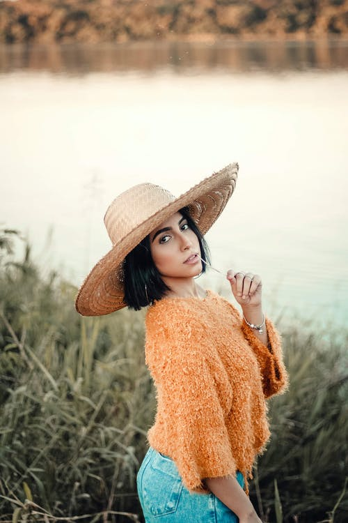 Photo of Woman in Beige Sun Hat, Orange Knitted Top and Blue Denim Bottoms