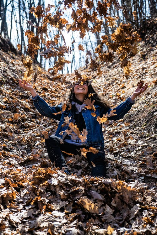Photo of a Woman Surrounded by Dried Leaves