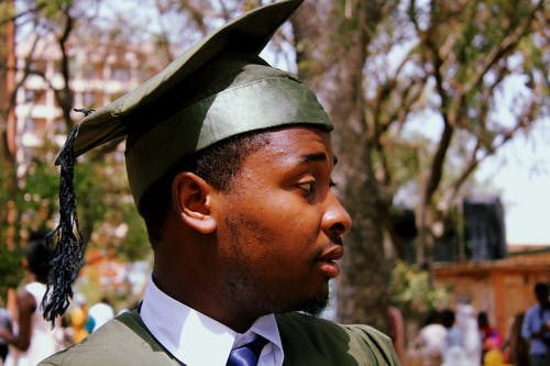 Close-Up Photo of a Man Wearing Green Academic Dress