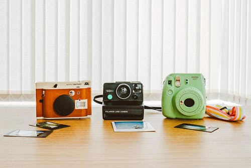Three Assorted-color Instant Cameras on the Table With Sample Photos